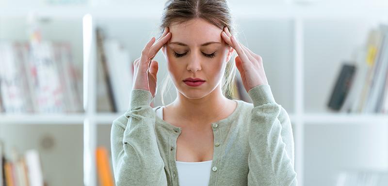 jeune femme avec une migraine qui masse ses tempes